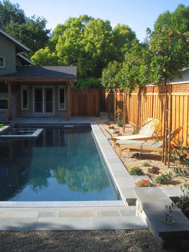 Using pebble mulch on one side of the pool allowed planting and pathway space.